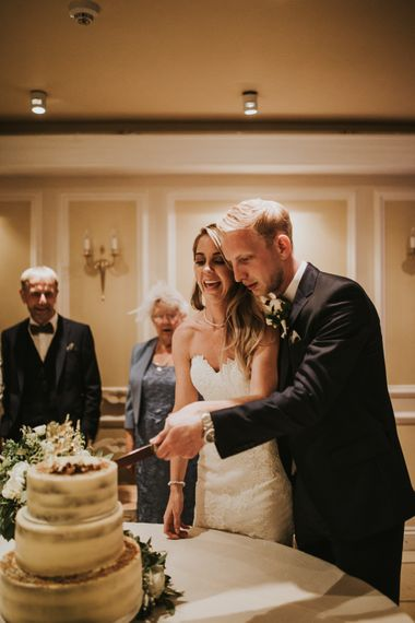 Cutting the Wedding Cake | Bride in Pronovias Oringo Lace Bridal Gown & Cape | Groom in Blue Marks and Spencer Suit | Green, White & Gold Wedding at Buckland Tout Saints, Devon |  Darina Stoda Photography