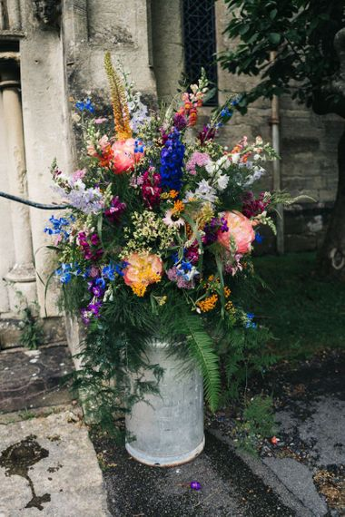 Bright wedding flowers to match bright floral moon gate arch