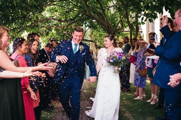 Bride and groom confetti exit with bright bouquet