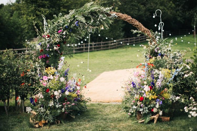 Floral moon gate arch with wildflowers at garden wedding