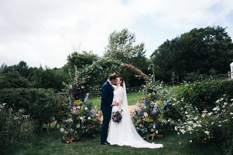 Wildflower floral moon gate arch at marquee wedding