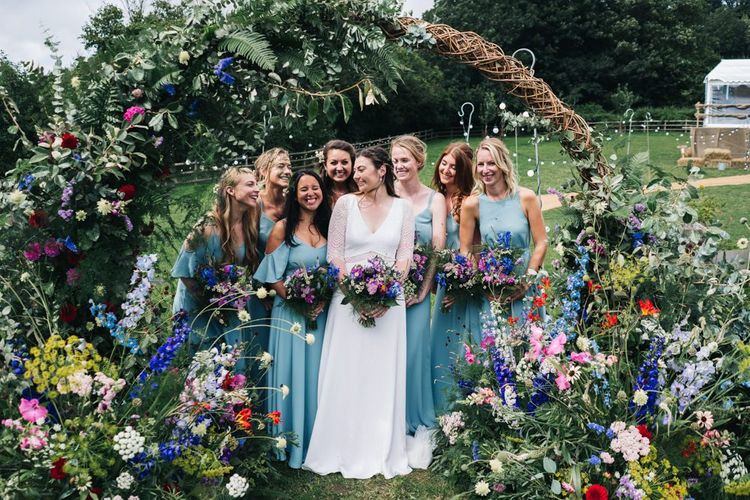 Wildflower moon gate arch with bridesmaids in Rewritten blue bridesmaid dresses