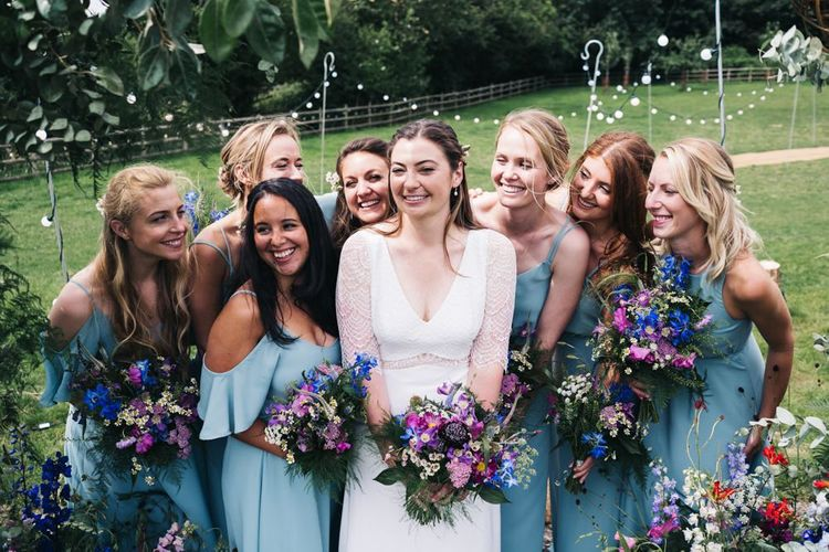 Blue bridesmaid dresses with wildflower bouquets to match the floral moon gate arch