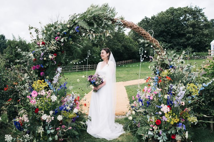 Bride in lace sleeved wedding dress with flower moon gate arch