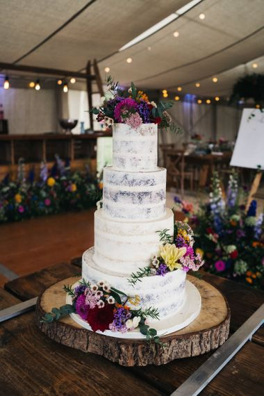 Semi-naked wedding cake with flower decor to match the wildflower moon gate arch