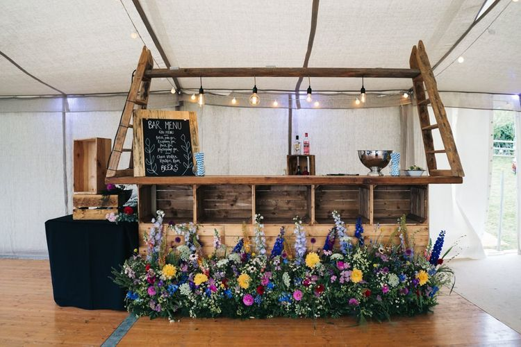 Wooden bar at wedding with bright flowers
