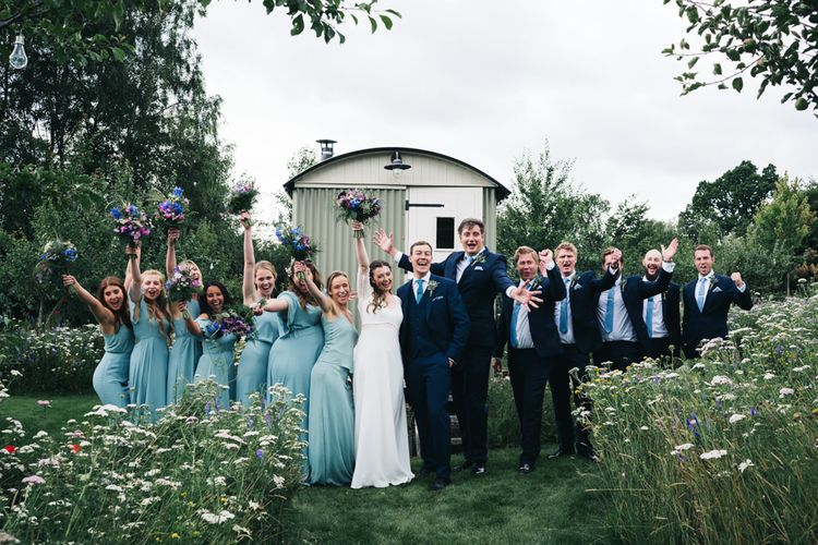 Bridal party in blue dress with groomsmen in matching ties