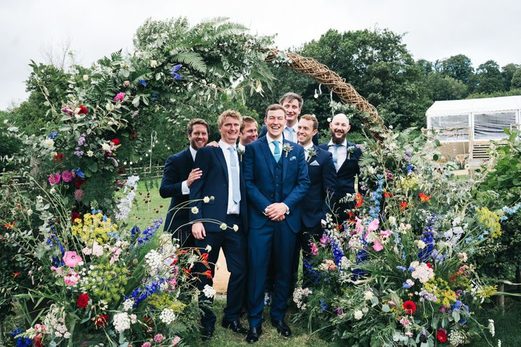 Groom and groomsmen in floral moon gate arch