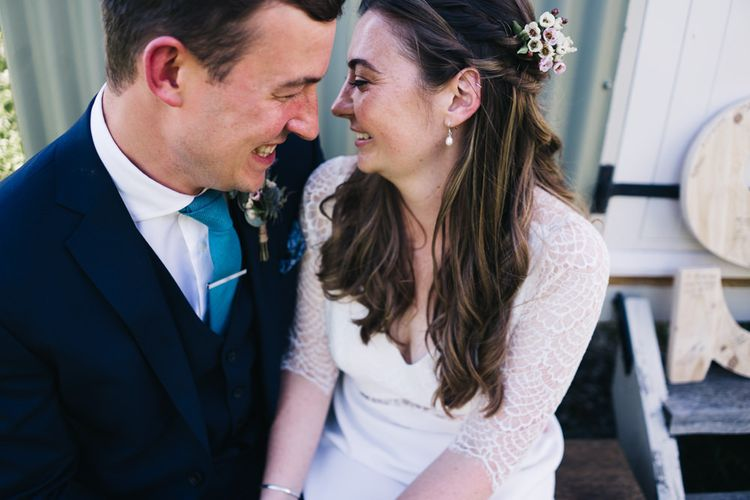 Bride and groom share a moment at marquee wedding with bridal hair down with flower hair pieces