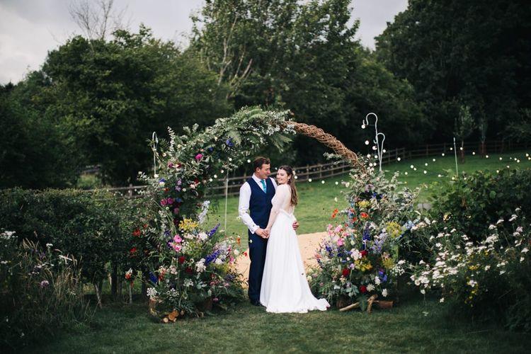 Wildflower moon gate arch at marquee wedding
