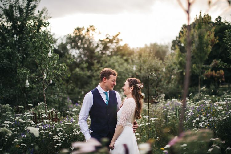Bride and groom in wildflower orchard with wildflower moon gate arch