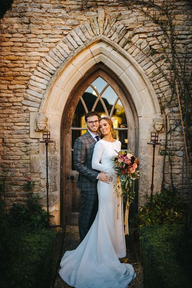 Bride in Pronovias Wedding Dress with Long Sleeves and Groom in Grey Checked Suit