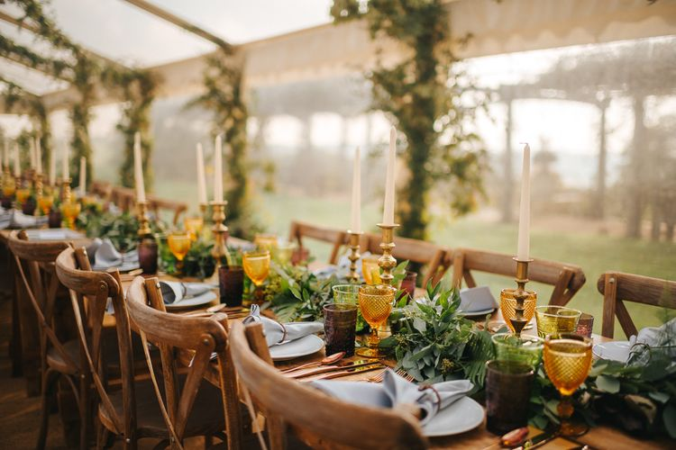 Marquee Wedding Reception Decor with Greenery tAble Runner, Gold Candle Sticks and Yellow Goblets
