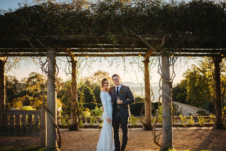 Bride in Fitted Pronovias Wedding Dress with Long Sleeves and Groom in Grey Checked Suit