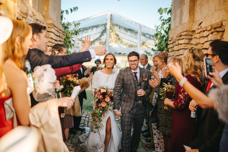 Confetti Moment with Bride in Front Split Wedding Dress and Groom in Check Suit