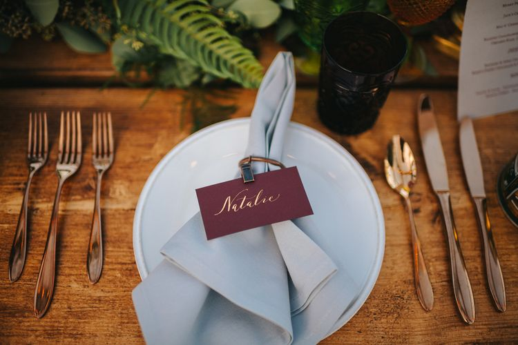 Elegant Place Setting with Gold Cutlery, Grey Napkin and Burgundy Name Place Card