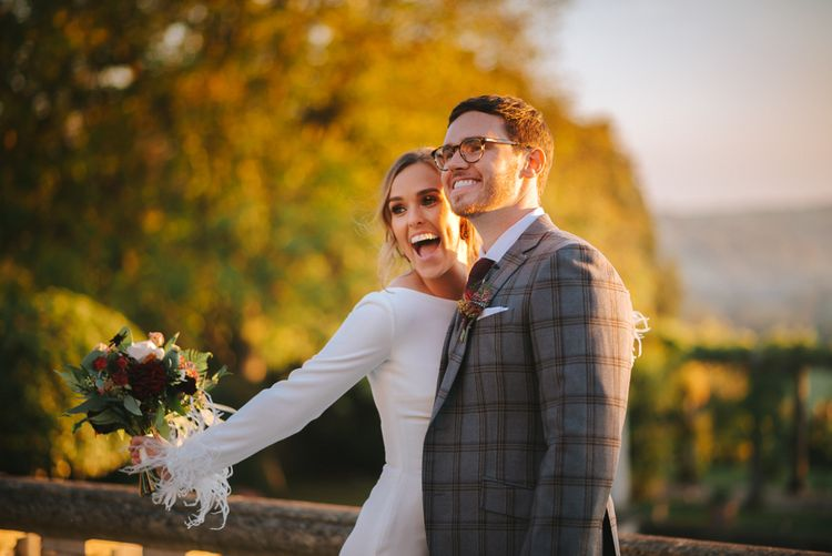 Bride and Groom Smiling with Bride in Pronovias Wedding Dress with Feather Sleeves