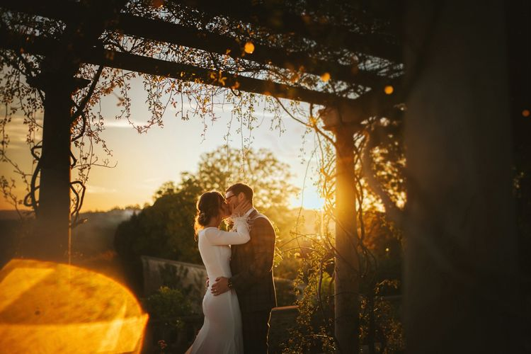 Sunset Wedding Portrait of Bride in Fitted Pronovias Wedding Dress and Groom in Checked Suit