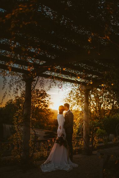 Sunset Wedding Portrait of Bride in Long Sleeve  Pronovias Wedding Dress and Groom in Grey Checked Suit