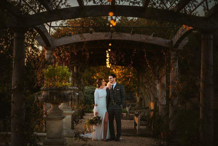 Sunset Wedding Portrait of Bride in Front Slit  Pronovias Wedding Dress and Groom in Christopher Schafer Clothier Suit