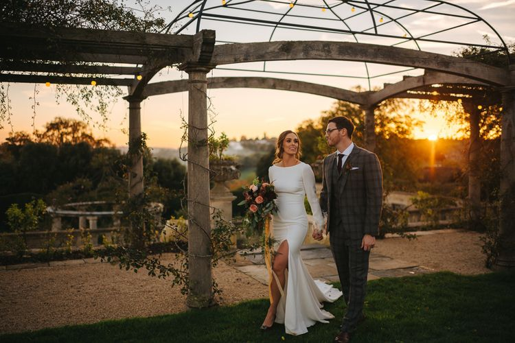 Sunset Wedding Portrait of Bride in Front Slit  Pronovias Wedding Dress and Groom in Grey Checked Suit