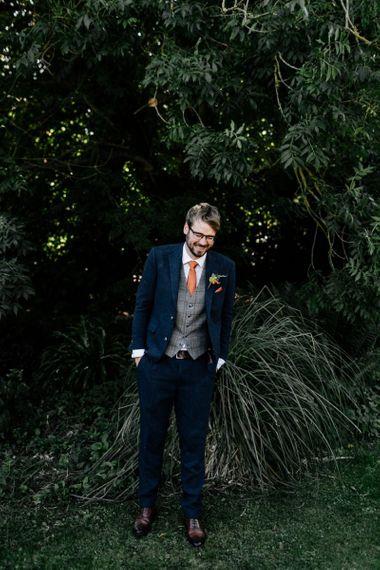 Groom in navy wool suit check waistcoat and orange tie