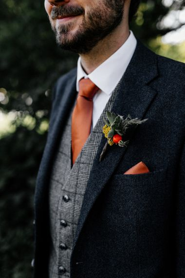Succulent buttonhole with orange pocket square and tie