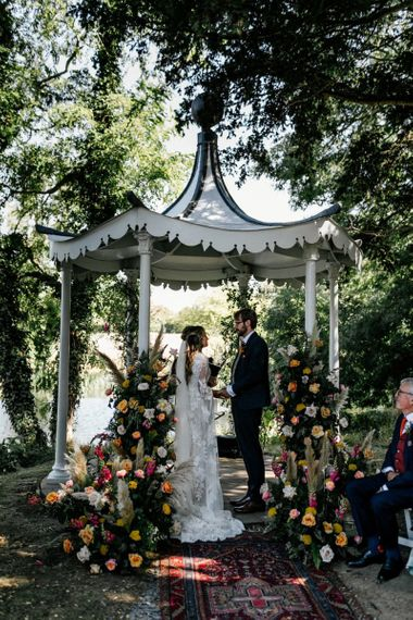 Bride and groom exchanging vows at outdoor wedding ceremony