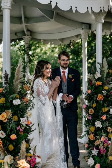 Boho bride and groom clapping at Preston Court wedding  ceremony