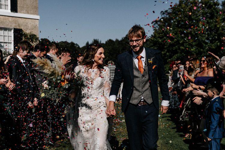 Bride in long sleeve Pronovias wedding dress and groom in check waistcoat and orange tie
