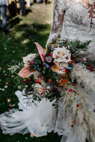 Boho wedding bouquet with pampas grass and anthuriums covered in confetti