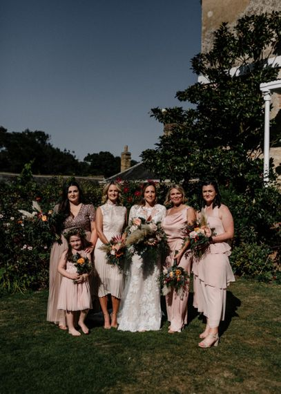 Bridesmaids in different blush pink dresses
