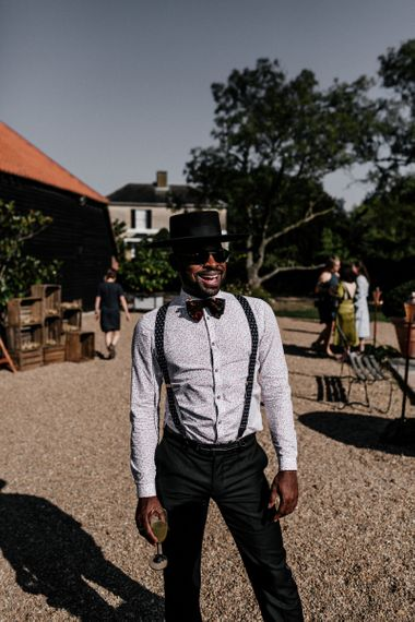 Stylish wedding guest in floral shirt, braces, bow tie and top hat