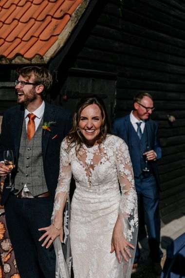 Bride in lace wedding dress with long sleeves laughing