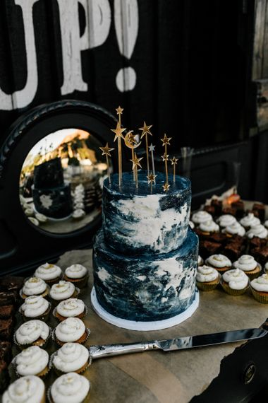 Blue and white celestial wedding cake with gold stars topper