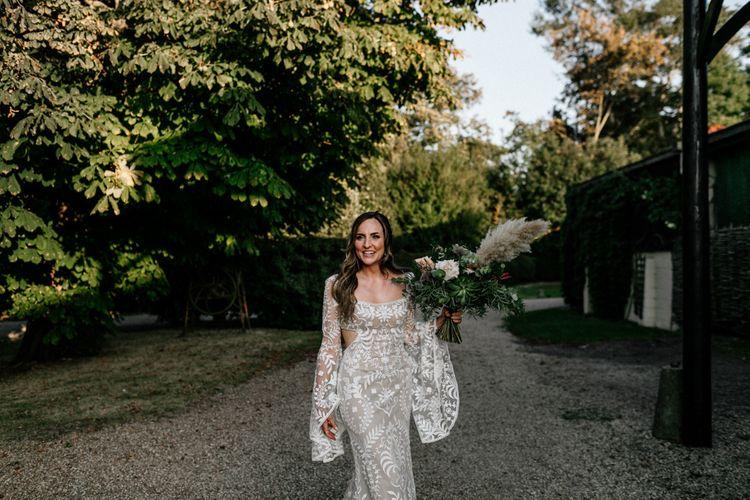 Boho bride in lace Willowby Watters wedding dress