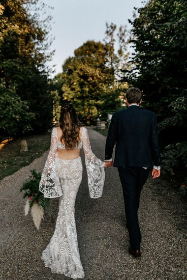Bride in boho wedding dress with Bell sleeves and cut away back detail