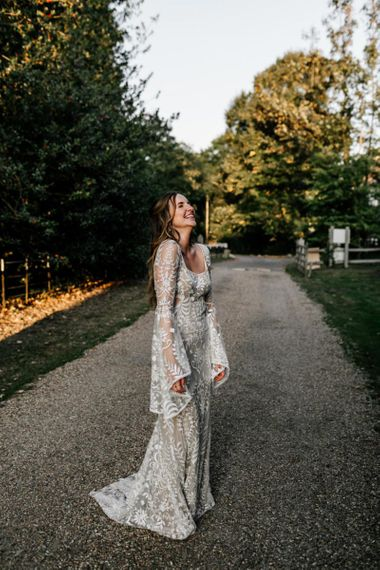 Bride in boho wedding dress with bell sleeves and lace detail
