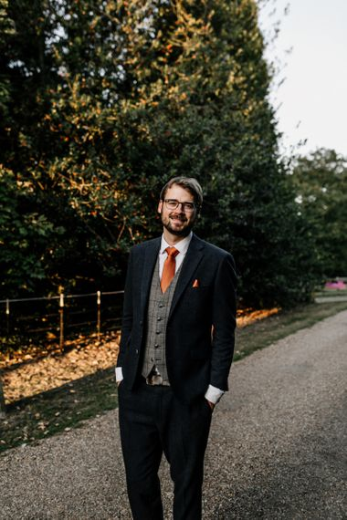 Groom in navy wool suit with check waistcoat and orange tie