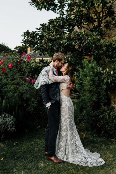 Bride in Willowby Watters wedding dress with bell sleeves  hugging her groom