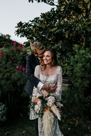 Groom embracing his bride in lace wedding dress