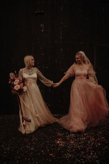两个新娘新娘穿着粉色袜子和婚纱的裙子在一起的香槟