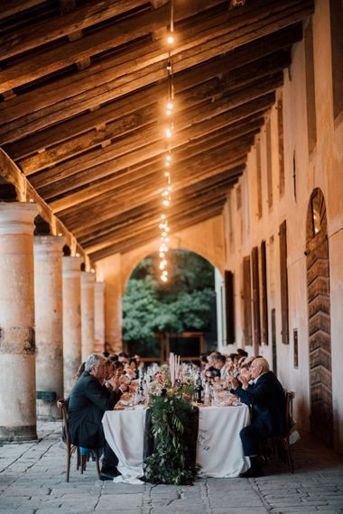 Guests enjoy wedding breakfast outside Italian venue