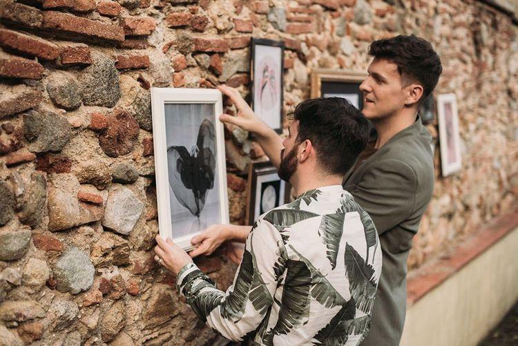 Groomsmen Putting Up a Gallery Wall Wedding Decor