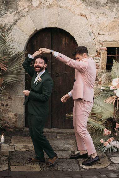 Groom in Pink Wedding Suit Twirling His Partner in a Green Wedding Suit