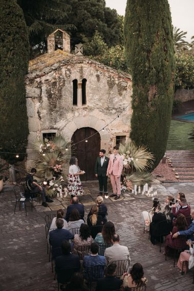 Outdoor Wedding Ceremony with Festoon Lights and Grooms in Pink and Green Wedding Suits