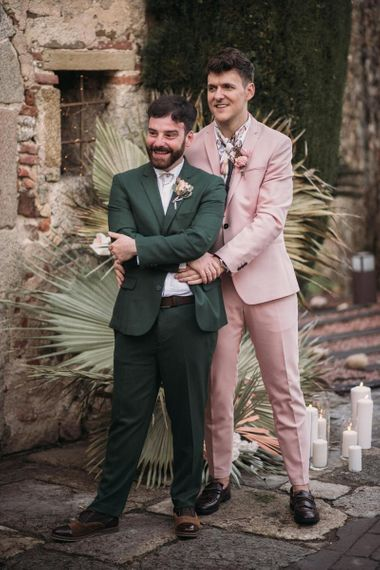 Groom in Pink Wedding Suit Embracing His Partner in a Green Wedding Suit During the Wedding Ceremony