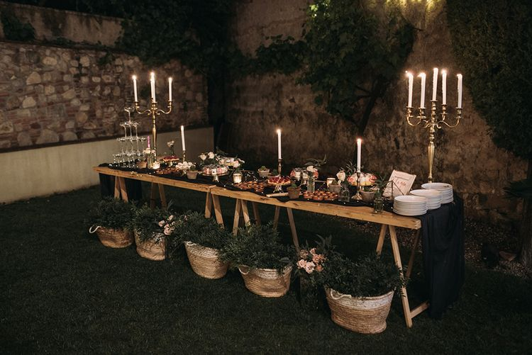 Dessert Table with Food Platters, Silver Candelabra and Woven Baskets Full of Foliage