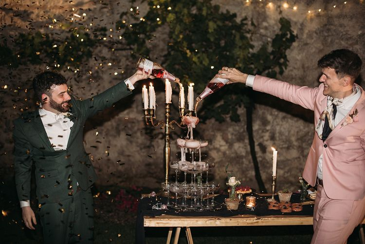 Grooms in Pink and Green Wedding Suits Pouring Champagne over Champagne Tower