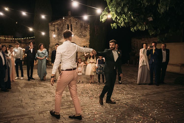 Two Grooms Dancing Their First Dance in the Courtyard Under Festoon Lights